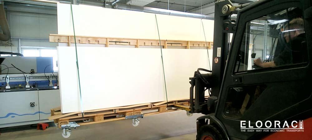 Eloorac A-Gestell bzw. Transportgestell beladen mit langen Produkten für den Messebau, wird von einem Stapler angehoben. Es ist gut zu erkennen, dass ein langes Eloorac Transportgestell welches aus 4 Europaletten besteht, nicht durchbiegt bzw. durch hängt.