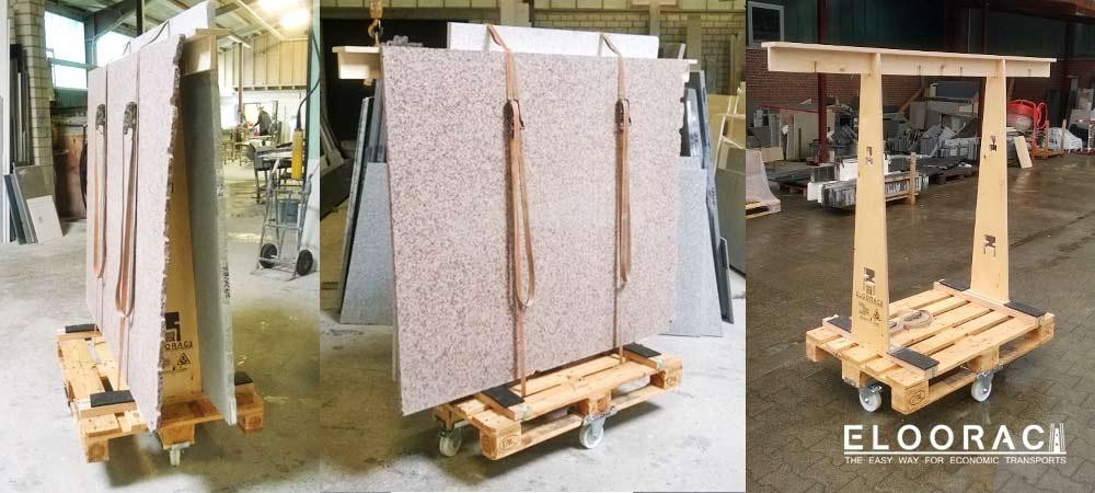 Natursteinplatten auf einem Eloorac Transportgestell stehend, werden auf Eloowheel Transportrollen unter einer Europalette durch die Steinmetz Werkstatt gefahren.