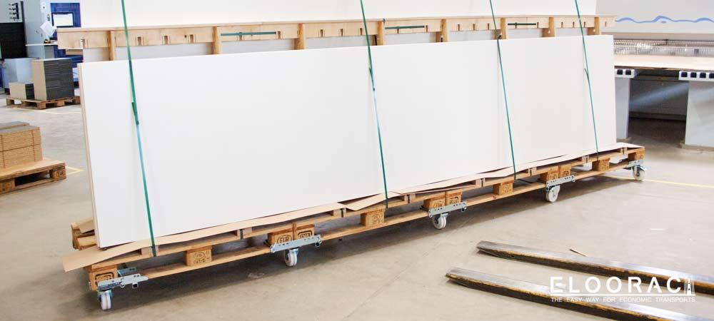 Ein sehr langes Eloorac Messebau Gestell auf dem lange, beschichtete Spanplatten stehen. Durch Eloowheel Transportrollen kann das Transportgestell sehr einfach in der Tischlerei und auf der Messe bewegt werden.