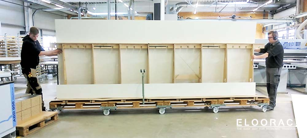 A 4.8-meter-long Eloorac stand construction transport frame is loaded with 4.5-meter-long chipboard panels intended for an exhibition stand and is transported on Eloowheel transport rolls through the production of an exhibition stand construction company or a joinery.
